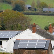Four solar installations on roofs - including top right behind tree.